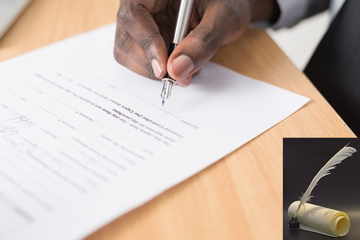 person hand signing a document